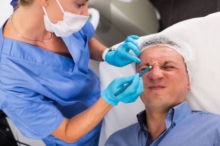 Female specialist is marking zone on face of client in estetic clinic. Stock Photo