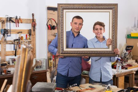 Portrait of smiling father and son  choosing framing moulding in studio