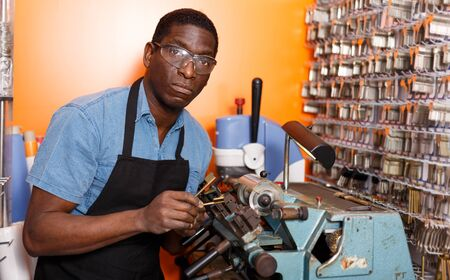 Positive African-American man working in key workshop, making key copies on bench machine