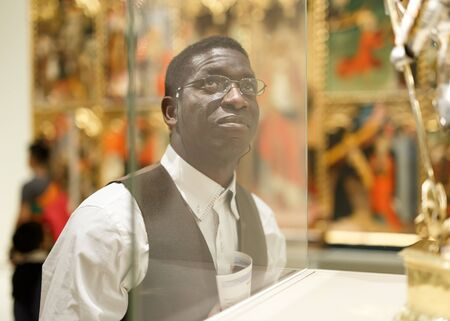 African man standing at hall of Art Museum among exhibits of antiquity Banque d'images