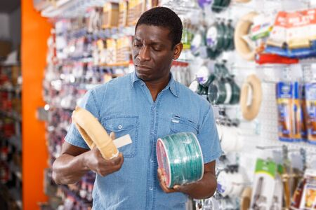 Portrait of concentrated adult seller of household goods shop organizing assortment of items on shelves and racks