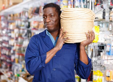 Confident happy cheerful positive glad African-American handyman choosing materials for overhauls in household store