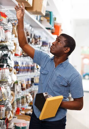 Experienced African American foreman looking for construction supplies for renovation works in household store 版權商用圖片