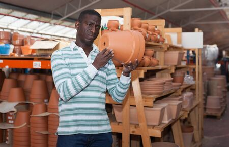 African American owner of greenhouse choosing pots for plants in garden material warehouse