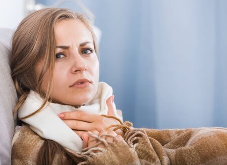 Young woman catching cold, wrapping in blanket