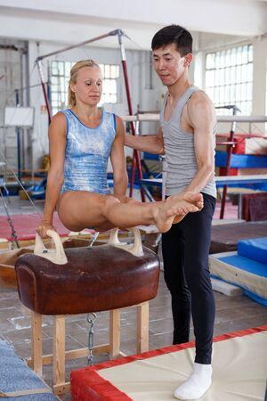 Woman gymnast in bodysuit training at vaulting buck in sport gym, man helping