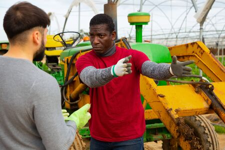 Conflict of a farmer and a hired worker in a greenhouse
