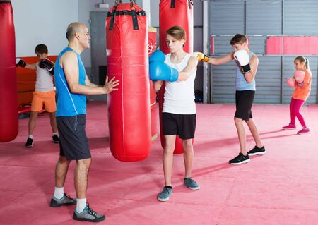 Young sportsmans at boxing workout on punching bag with coach