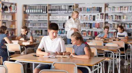 Schoolchildren preparing for lesson in a school library, reading and writing