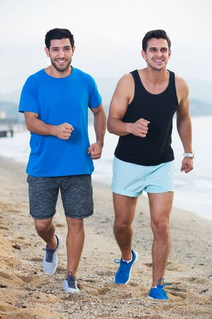 Smiling sportsmen are jogging together on the beach near ocean 스톡 콘텐츠
