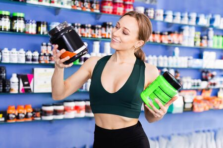 Smiling cheerful positive sporty girl looking for necessary food supplements in sport nutrition store