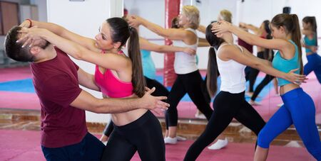 Young woman is training self-defence moves in pair with trainer in sporty gym