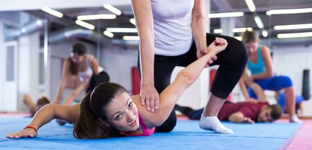 Ordinary female are training self-defence moves in pairs in sporty gym