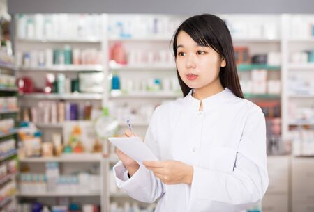Chinese woman pharmacist keeps track of drugs in interior of pharmacy