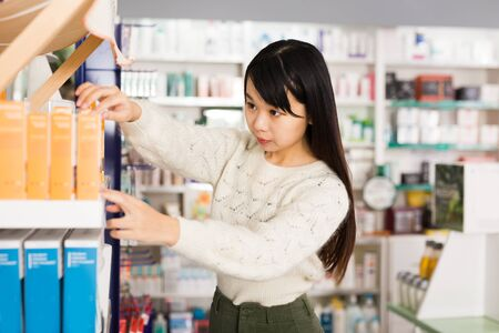 Young chinese woman chooses medicine at the pharmacy Zdjęcie Seryjne