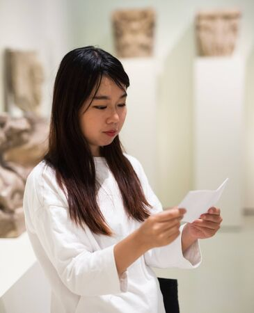 Chinese girl with interest using guidebook at ancient sculptures in museum Banque d'images