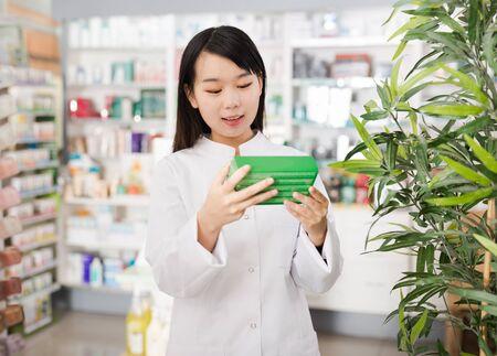 Chinese female pharmacist demonstrating assortment of pharmacy