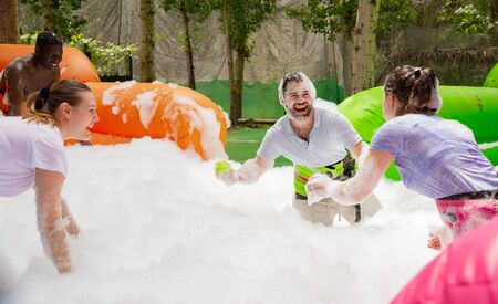 Game of funny friends in soap suds on an inflatable trampoline