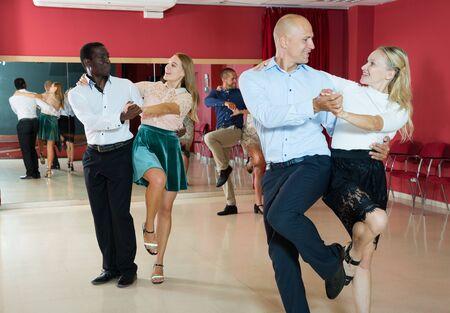 Adult dancing couples enjoying active boogie-woogie in modern studio
