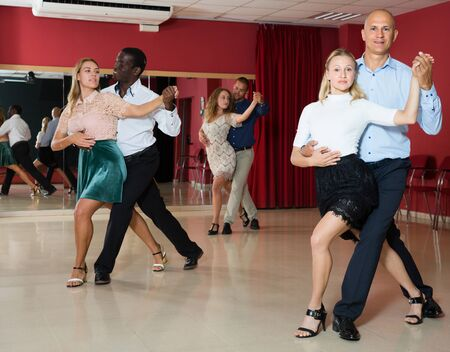 Positive adult couples dancing  salsa dance together  in modern studio
