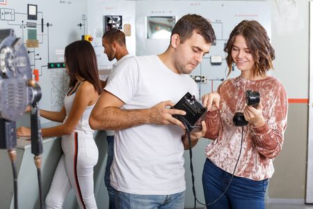Focused girl and guy checking telephone set while trying to get out of escape room stylized as underground shelter Banque d'images