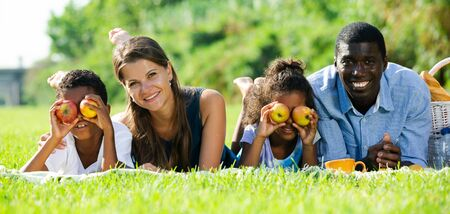 Cheerful mixed race couple with preteen children gaily spending time at picnic, lying together on green lawn