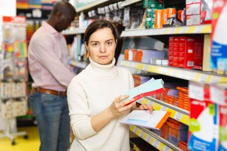 Adult female standing with office stationery, during shopping with man in stationery shop