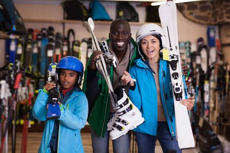 Cheerful family of three in skiing outfit satisfied with choice in modern store of sports equipment Banco de Imagens