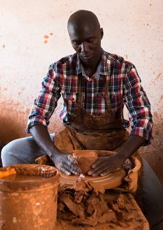 Professional male potter making bowl on potters wheel in pottery studio