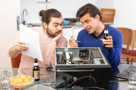 Men drink beer and repair the desktop computer
