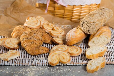 Various bakery and pastry products on rattan mat on wooden table 写真素材
