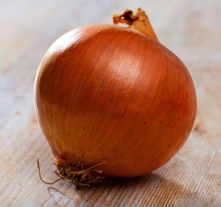 Closeup of raw organic whole yellow onion on wooden background