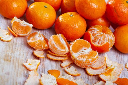 Peeled and whole fresh juicy clementines on wooden table. Concept of health benefits of citrus