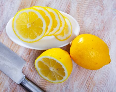 Fresh lemon slices on wooden background. Vitamin cooking ingredients