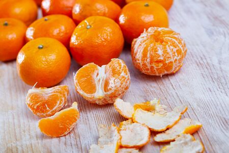 Peeled and whole fresh juicy clementines on wooden table. Concept of health benefits of citrus Imagens
