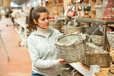 Female customer choosing  wicker products in home decor warehouse
