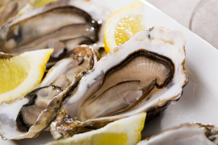 Tasty oysters with lemon on plate top view