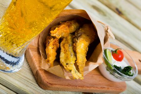 Fish chips - fried in batter anchovies with classic creamy cheese sauce and greens Stock Photo