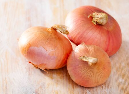 Closeup of raw organic whole onions on wooden surface