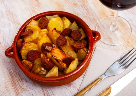 Typical spanish dish, baked potato with chorizo in ceramic bowl