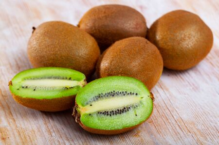 Fresh juicy whole and halved kiwi fruits on wooden table. Healthy vitamin product