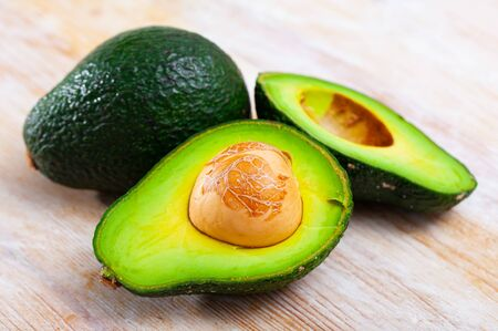 Whole and cut in half ripe organic avocados on wooden background. Healthy vitamin nutrition concept