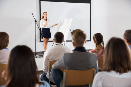 Confident female student answering with microphone in front of student group in auditorium Imagens