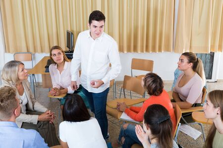 Young male student discussing with groupmates sitting in circle in auditorium during classes Reklamní fotografie