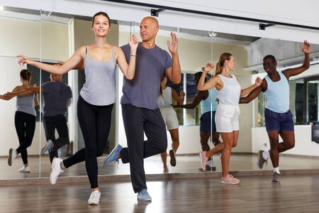 Young smiling people practicing in pairs vigorous jive movements in dance studio. Focus on man