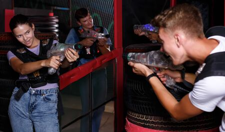 Group portrait of jolly emotional people with laser guns playing laser tag game together in dark labyrinth