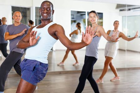 Cheerful smiling people practicing vigorous lindy hop movements in dance class