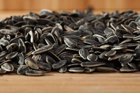 Natural background of sunflower seeds in hulls on wooden surface. Popular snack food
