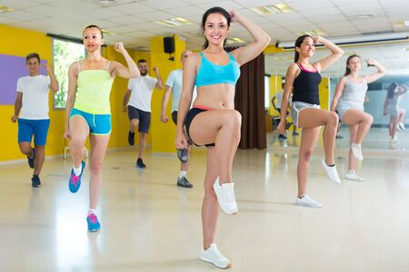 Group of dancers are dancing aerobics in dance class.