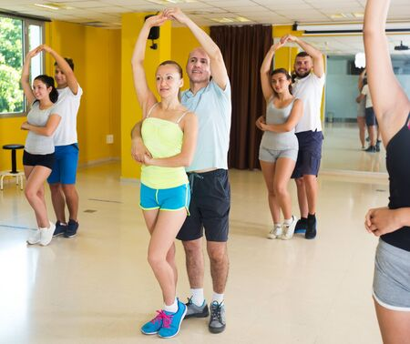Cheerful adults dancing salsa together in dance studio